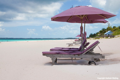 Unbrellas and beach chairs on Coral Beach, Harbor Island, Bahama