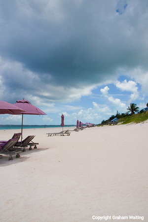 Unbrellas and beach chairs on Coral Beach, Harbor Island, Bahama