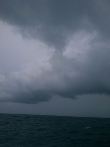 © Joseph Dougherty. All rights reserved.   Storm clouds and white caps from the deck of the sailboat.