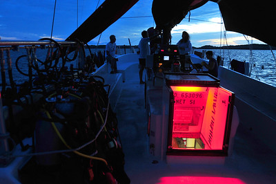 © Joseph Dougherty. All rights reserved.  Predawn twilight on the sailboat's main deck, with light spilling from the ladder to the galley.