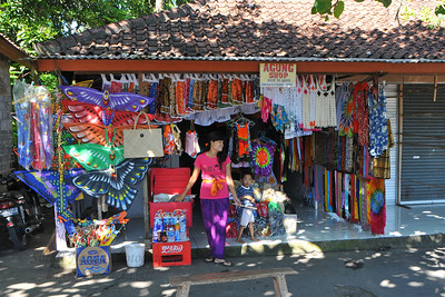 Shops at the entrance to Goa Gajah. Agung Shop at Goa Gajah. Everything from kites to cloths and food was available at the shops. Elephant Cave, is located on the island of Bali near Ubud and a short distance from Bedulu. Built in the 9th century, it served as a sanctuary. A carved entrance depicts entangling leaves, rocks, animals, ocean waves and demonic human shapes running from the gaping mouth which forms the entrance to the cave. The facade of the cave is a relief of various menacing creatures and demons carved right into the rock at the cave entrance. The primary figure was once thought to be an elephant, hence the nickname Elephant Cave. The site is mentioned in the Javanese poem Desawarnana written in 1365. Inside the cave one finds the Shiva lingum.  The monstrous Kala head that looms above the entrance seems to part the rock with her hands. Similarly decorated hermit cells are also found in Java. The large earrings indicate that the figure is that of a woman. The T-shaped interior of the rock-hewn cave contained niches which probably served as compartments for ascetics.  Goa Gajah is named after Sungai Petanu (Elephant River not an elephant as elephants are not found in Bali) and dates back to the 11th Century where it originally served as a dwelling for Hindu priests. Outside the cave at the pavilion is a statue of Men Brayut, the Balinese woman who together with her husband Pan could not stop having kids. The legend of Men Brayut is also represented in local Buddhist writings, under the name of Hariti, indicating a possible Buddhist association with Goa Gajah as well as Hindu.  Outside the cave, an extensive bathing place on the site was not excavated until the 1950s. These appear to have been built to ward off evil spirits. It is an UNESCO World Heritage site.