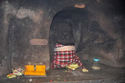 Inside view of the cave, the statue of Lord Ganesha (Batu Ganesh). Goa Gajah, or Elephant Cave, is located on the island of Bali near Ubud and a short distance from Bedulu. Built in the 9th century, it served as a sanctuary. A carved entrance depicts entangling leaves, rocks, animals, ocean waves and demonic human shapes running from the gaping mouth which forms the entrance to the cave. The facade of the cave is a relief of various menacing creatures and demons carved right into the rock at the cave entrance. The primary figure was once thought to be an elephant, hence the nickname Elephant Cave. The site is mentioned in the Javanese poem Desawarnana written in 1365. Inside the cave one finds the Shiva lingum.  The monstrous Kala head that looms above the entrance seems to part the rock with her hands. Similarly decorated hermit cells are also found in Java. The large earrings indicate that the figure is that of a woman. The T-shaped interior of the rock-hewn cave contained niches which probably served as compartments for ascetics.  Goa Gajah is named after Sungai Petanu (Elephant River not an elephant as elephants are not found in Bali) and dates back to the 11th Century where it originally served as a dwelling for Hindu priests. Outside the cave at the pavilion is a statue of Men Brayut, the Balinese woman who together with her husband Pan could not stop having kids. The legend of Men Brayut is also represented in local Buddhist writings, under the name of Hariti, indicating a possible Buddhist association with Goa Gajah as well as Hindu.  Outside the cave, an extensive bathing place on the site was not excavated until the 1950s. These appear to have been built to ward off evil spirits. It is an UNESCO World Heritage site.