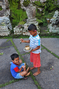 Children at Goa Gajah perform a Hindu ritual ceremony.  Elephant Cave, is located on the island of Bali near Ubud and a short distance from Bedulu. Built in the 9th century, it served as a sanctuary. A carved entrance depicts entangling leaves, rocks, animals, ocean waves and demonic human shapes running from the gaping mouth which forms the entrance to the cave. The facade of the cave is a relief of various menacing creatures and demons carved right into the rock at the cave entrance. The primary figure was once thought to be an elephant, hence the nickname Elephant Cave. The site is mentioned in the Javanese poem Desawarnana written in 1365. Inside the cave one finds the Shiva lingum.  The monstrous Kala head that looms above the entrance seems to part the rock with her hands. Similarly decorated hermit cells are also found in Java. The large earrings indicate that the figure is that of a woman. The T-shaped interior of the rock-hewn cave contained niches which probably served as compartments for ascetics.  Goa Gajah is named after Sungai Petanu (Elephant River not an elephant as elephants are not found in Bali) and dates back to the 11th Century where it originally served as a dwelling for Hindu priests. Outside the cave at the pavilion is a statue of Men Brayut, the Balinese woman who together with her husband Pan could not stop having kids. The legend of Men Brayut is also represented in local Buddhist writings, under the name of Hariti, indicating a possible Buddhist association with Goa Gajah as well as Hindu.  Outside the cave, an extensive bathing place on the site was not excavated until the 1950s. These appear to have been built to ward off evil spirits. It is an UNESCO World Heritage site.