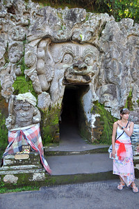 Tourists visiting Goa Gajah at the entrance of the cave opening. Elephant Cave, is located on the island of Bali near Ubud and a short distance from Bedulu. Built in the 9th century, it served as a sanctuary. A carved entrance depicts entangling leaves, rocks, animals, ocean waves and demonic human shapes running from the gaping mouth which forms the entrance to the cave. The facade of the cave is a relief of various menacing creatures and demons carved right into the rock at the cave entrance. The primary figure was once thought to be an elephant, hence the nickname Elephant Cave. The site is mentioned in the Javanese poem Desawarnana written in 1365. Inside the cave one finds the Shiva lingum.  The monstrous Kala head that looms above the entrance seems to part the rock with her hands. Similarly decorated hermit cells are also found in Java. The large earrings indicate that the figure is that of a woman. The T-shaped interior of the rock-hewn cave contained niches which probably served as compartments for ascetics.  Goa Gajah is named after Sungai Petanu (Elephant River not an elephant as elephants are not found in Bali) and dates back to the 11th Century where it originally served as a dwelling for Hindu priests. Outside the cave at the pavilion is a statue of Men Brayut, the Balinese woman who together with her husband Pan could not stop having kids. The legend of Men Brayut is also represented in local Buddhist writings, under the name of Hariti, indicating a possible Buddhist association with Goa Gajah as well as Hindu.  Outside the cave, an extensive bathing place on the site was not excavated until the 1950s. These appear to have been built to ward off evil spirits. It is an UNESCO World Heritage site.