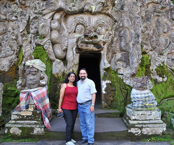 Anu & Suchit at Goa Gajah, or Elephant Cave. The cave is located on the island of Bali near Ubud and a short distance from Bedulu. Built in the 9th century, it served as a sanctuary. A carved entrance depicts entangling leaves, rocks, animals, ocean waves and demonic human shapes running from the gaping mouth which forms the entrance to the cave. The facade of the cave is a relief of various menacing creatures and demons carved right into the rock at the cave entrance. The primary figure was once thought to be an elephant, hence the nickname Elephant Cave. The site is mentioned in the Javanese poem Desawarnana written in 1365. Inside the cave one finds the Shiva lingum.  The monstrous Kala head that looms above the entrance seems to part the rock with her hands. Similarly decorated hermit cells are also found in Java. The large earrings indicate that the figure is that of a woman. The T-shaped interior of the rock-hewn cave contained niches which probably served as compartments for ascetics.  Goa Gajah is named after Sungai Petanu (Elephant River not an elephant as elephants are not found in Bali) and dates back to the 11th Century where it originally served as a dwelling for Hindu priests. Outside the cave at the pavilion is a statue of Men Brayut, the Balinese woman who together with her husband Pan could not stop having kids. The legend of Men Brayut is also represented in local Buddhist writings, under the name of Hariti, indicating a possible Buddhist association with Goa Gajah as well as Hindu.  Outside the cave, an extensive bathing place on the site was not excavated until the 1950s. These appear to have been built to ward off evil spirits. It is an UNESCO World Heritage site.
