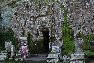 Goa Gajah, or Elephant Cave, is located on the island of Bali near Ubud and a short distance from Bedulu. Built in the 9th century, it served as a sanctuary. A carved entrance depicts entangling leaves, rocks, animals, ocean waves and demonic human shapes running from the gaping mouth which forms the entrance to the cave. The facade of the cave is a relief of various menacing creatures and demons carved right into the rock at the cave entrance. The primary figure was once thought to be an elephant, hence the nickname Elephant Cave. The site is mentioned in the Javanese poem Desawarnana written in 1365. Inside the cave one finds the Shiva lingum.  The monstrous Kala head that looms above the entrance seems to part the rock with her hands. Similarly decorated hermit cells are also found in Java. The large earrings indicate that the figure is that of a woman. The T-shaped interior of the rock-hewn cave contained niches which probably served as compartments for ascetics.  Goa Gajah is named after Sungai Petanu (Elephant River not an elephant as elephants are not found in Bali) and dates back to the 11th Century where it originally served as a dwelling for Hindu priests. Outside the cave at the pavilion is a statue of Men Brayut, the Balinese woman who together with her husband Pan could not stop having kids. The legend of Men Brayut is also represented in local Buddhist writings, under the name of Hariti, indicating a possible Buddhist association with Goa Gajah as well as Hindu.  Outside the cave, an extensive bathing place on the site was not excavated until the 1950s. These appear to have been built to ward off evil spirits. It is an UNESCO World Heritage site.