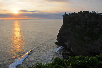 Sunset at Pura Luhur Uluwatu, Bali.  Pura Luhur Uluwatu is one of Bali's kayangan jagat (directional temples) and guards Bali from evil spirits from the south-west. Major Hindu deities dwell in Uluwatu such as - Bhatara Rudra, God of the elements and of cosmic force majeures. Bali's most spectacular temples located high on a cliff top at the edge of a plateau 250 feet above the waves of the Indian Ocean. Uluwatu lies at the southern tip of Bali in Badung Regency. Dedicated to the spirits of the sea, the famous Pura Luhur Uluwatu temple is an architectural wonder in black coral rock, beautifully designed with spectacular views. This is a popular place to enjoy the sunset. Famous not only for its unique position, Uluwatu also boasts one of the oldest temples in Bali, Pura Uluwatu. Most of Bali's regencies have Pura Luhur (literally high temples or ascension temples) which become the focus for massive pilgrimages during three or five day odalan anniversaries. The photogenic Tanah Lot and the Bat Cave temple, Goa Lawah, are also Pura Luhur. Not all Pura Luhur are on the coast, however but all have inspiring locations, overlooking large bodies of water.  Uluwatu is a small village on the west coast, south of Jimbaran, but for most visitors it refers only to the famous temple of the same name and several kilometers further south at the coast. A taxi from Kuta to Uluwatu takes about 30 minutes up and down winding roads.  The temple is inhabited by large number of monkeys, who are extremely adept at snatching visitors' belonging, including bags, cameras and eyeglasses. One has to keep a very close grip on all your belongings. Anu carried a stick like some others and I carried my tripod. :) If you do have something taken, the monkeys can usually be induced to exchange it for some fruit. Needless to say, rewarding the monkeys like this only encourages them to steal more. Locals and even the temple priests will be happy to do the job for you, naturally in exchange for a tip. T