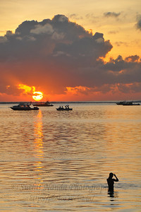 Early morning dip in the water as the sun rise at Sanur Beach. The Sun just above the horizon and breaking out before hiding behind the clouds. Sanur (Indonesian: Pantai Sanur Pronounced: Sah-Noor) is a coastal stretch of beach of Denpasar city located in South East of Bali. Its about a 30 minutes drive from Ngurah Rai International Airport. Those wanting to avoid the mad-crowds of Kuta prefer Sanur beach which has grown into a little town in its own right. It contains a number of resorts and is a popular tourist destination. lessed with reef bed aquatics and various kinds of marine organism, Sanur is the second best diving spot in Bali after Tulamben. Its moderate wind and transparent water surely provides water sport enthusiasts with a playground of the first degree in terms of quality and safety. It also has a wide variety of restaurants, cafes, shops and nightlife.