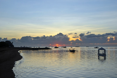 Sunrise at Sanur Beach. The Sun just above the horizon and breaking out before hiding behind the clouds. Sanur (Indonesian: Pantai Sanur Pronounced: Sah-Noor) is a coastal stretch of beach of Denpasar city located in South East of Bali. Its about a 30 minutes drive from Ngurah Rai International Airport. Those wanting to avoid the mad-crowds of Kuta prefer Sanur beach which has grown into a little town in its own right. It contains a number of resorts and is a popular tourist destination. lessed with reef bed aquatics and various kinds of marine organism, Sanur is the second best diving spot in Bali after Tulamben. Its moderate wind and transparent water surely provides water sport enthusiasts with a playground of the first degree in terms of quality and safety. It also has a wide variety of restaurants, cafes, shops and nightlife.