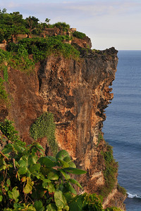 Steep cliff and shoreline visible at Pura Luhur Uluwatu, Bali.  Pura Luhur Uluwatu is one of Bali's kayangan jagat (directional temples) and guards Bali from evil spirits from the south-west. Major Hindu deities dwell in Uluwatu such as - Bhatara Rudra, God of the elements and of cosmic force majeures. Bali's most spectacular temples located high on a cliff top at the edge of a plateau 250 feet above the waves of the Indian Ocean. Uluwatu lies at the southern tip of Bali in Badung Regency. Dedicated to the spirits of the sea, the famous Pura Luhur Uluwatu temple is an architectural wonder in black coral rock, beautifully designed with spectacular views. This is a popular place to enjoy the sunset. Famous not only for its unique position, Uluwatu also boasts one of the oldest temples in Bali, Pura Uluwatu. Most of Bali's regencies have Pura Luhur (literally high temples or ascension temples) which become the focus for massive pilgrimages during three or five day odalan anniversaries. The photogenic Tanah Lot and the Bat Cave temple, Goa Lawah, are also Pura Luhur. Not all Pura Luhur are on the coast, however but all have inspiring locations, overlooking large bodies of water.  Uluwatu is a small village on the west coast, south of Jimbaran, but for most visitors it refers only to the famous temple of the same name and several kilometers further south at the coast. A taxi from Kuta to Uluwatu takes about 30 minutes up and down winding roads.  The temple is inhabited by large number of monkeys, who are extremely adept at snatching visitors' belonging, including bags, cameras and eyeglasses. One has to keep a very close grip on all your belongings. Anu carried a stick like some others and I carried my tripod. :) If you do have something taken, the monkeys can usually be induced to exchange it for some fruit. Needless to say, rewarding the monkeys like this only encourages them to steal more. Locals and even the temple priests will be happy to do the job for you, natural