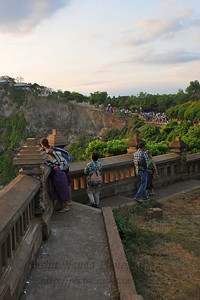 Many tourists waiting for the Sunset at Pura Luhur Uluwatu, Bali.  Pura Luhur Uluwatu is one of Bali's kayangan jagat (directional temples) and guards Bali from evil spirits from the south-west. Major Hindu deities dwell in Uluwatu such as - Bhatara Rudra, God of the elements and of cosmic force majeures. Bali's most spectacular temples located high on a cliff top at the edge of a plateau 250 feet above the waves of the Indian Ocean. Uluwatu lies at the southern tip of Bali in Badung Regency. Dedicated to the spirits of the sea, the famous Pura Luhur Uluwatu temple is an architectural wonder in black coral rock, beautifully designed with spectacular views. This is a popular place to enjoy the sunset. Famous not only for its unique position, Uluwatu also boasts one of the oldest temples in Bali, Pura Uluwatu. Most of Bali's regencies have Pura Luhur (literally high temples or ascension temples) which become the focus for massive pilgrimages during three or five day odalan anniversaries. The photogenic Tanah Lot and the Bat Cave temple, Goa Lawah, are also Pura Luhur. Not all Pura Luhur are on the coast, however but all have inspiring locations, overlooking large bodies of water.  Uluwatu is a small village on the west coast, south of Jimbaran, but for most visitors it refers only to the famous temple of the same name and several kilometers further south at the coast. A taxi from Kuta to Uluwatu takes about 30 minutes up and down winding roads.  The temple is inhabited by large number of monkeys, who are extremely adept at snatching visitors' belonging, including bags, cameras and eyeglasses. One has to keep a very close grip on all your belongings. Anu carried a stick like some others and I carried my tripod. :) If you do have something taken, the monkeys can usually be induced to exchange it for some fruit. Needless to say, rewarding the monkeys like this only encourages them to steal more. Locals and even the temple priests will be happy to do the job for you, natu
