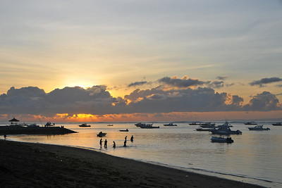 Some people playing in the shallow water. Sunrise at Sanur Beach. The Sun just above the horizon and breaking out before hiding behind the clouds. Sanur (Indonesian: Pantai Sanur Pronounced: Sah-Noor) is a coastal stretch of beach of Denpasar city located in South East of Bali. Its about a 30 minutes drive from Ngurah Rai International Airport. Those wanting to avoid the mad-crowds of Kuta prefer Sanur beach which has grown into a little town in its own right. It contains a number of resorts and is a popular tourist destination. lessed with reef bed aquatics and various kinds of marine organism, Sanur is the second best diving spot in Bali after Tulamben. Its moderate wind and transparent water surely provides water sport enthusiasts with a playground of the first degree in terms of quality and safety. It also has a wide variety of restaurants, cafes, shops and nightlife.