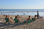 Relaxing and having a beer on Kuta Beach.Kuta District (Indonesian: Kecamatan Kuta) is administratively a district (Kecematan) and subdistrict/village (Kelurahan) in southern Bali, Indonesi ...