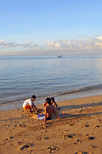 Soft light carasses the beach as the Sun rises into the sky at Sanur Beach. Some children playing in the sand as the gentle waves hit the shoreline.  Sanur (Indonesian: Pantai Sanur Pronounced: Sah-Noor) is a coastal stretch of beach of Denpasar city located in South East of Bali. Its about a 30 minutes drive from Ngurah Rai International Airport. Those wanting to avoid the mad-crowds of Kuta prefer Sanur beach which has grown into a little town in its own right. It contains a number of resorts and is a popular tourist destination. lessed with reef bed aquatics and various kinds of marine organism, Sanur is the second best diving spot in Bali after Tulamben. Its moderate wind and transparent water surely provides water sport enthusiasts with a playground of the first degree in terms of quality and safety. It also has a wide variety of restaurants, cafes, shops and nightlife.