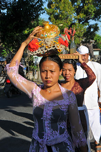 Traditionally dressed people carrying offerings in a procession on the streets of Bali. Bali is an Indonesian island with the provincial capital at Denpasar. Lying between Java to the west and Lombok to the east, the island is home to the largest tourist destination in the country and is renowned for its highly developed arts, including dance, sculpture, painting, leather, metalworking and music. What's interesting is that while Indonesia has the world's largest Muslim population, on the island of Bali, 93% of the population is Balinese Hindu and one can find Hinduism in each and every aspect of the life and living.