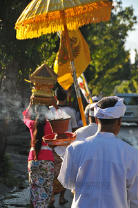 Women and men dressed traditionally carry offerings. Enroute from Denpasar International Airport to Ubud, we see a Hindu procession.  Bali is an Indonesian island with the provincial capital at Denpasar. Lying between Java to the west and Lombok to the east, the island is home to the largest tourist destination in the country and is renowned for its highly developed arts, including dance, sculpture, painting, leather, metalworking and music. What's interesting is that while Indonesia has the world's largest Muslim population, on the island of Bali, 93% of the population is Balinese Hindu and one can find Hinduism in each and every aspect of the life and living.