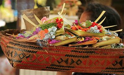De mand met offertjes wordt de tempel binnen gedragen. Ubud, Bali, Indonesië.