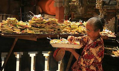 Vrouw brengt offertjes in de tempel voor de markt van Ubud. Ubud, Bali, Indonesië.