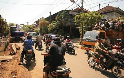 De vuilniswagen probeert een plekje op de weg te veroveren in druk Ubud. Bali, Indonesië.