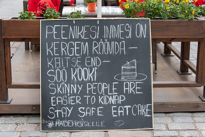 "Chalkboard sign in Tallinn, Estonia saying, ""skinny people are easier to kidnap stay safe eat cake."""