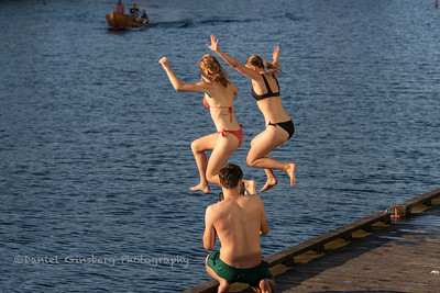 Two girls jump in the water as boy takes their picture in Copenhagen, Denmark.