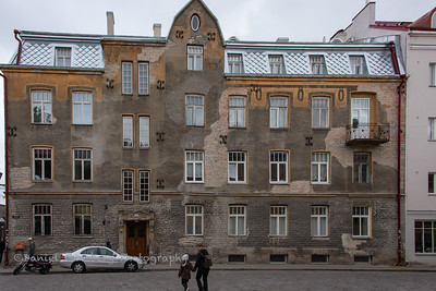 Man walking child in front of building in Tallinn, Estonia.