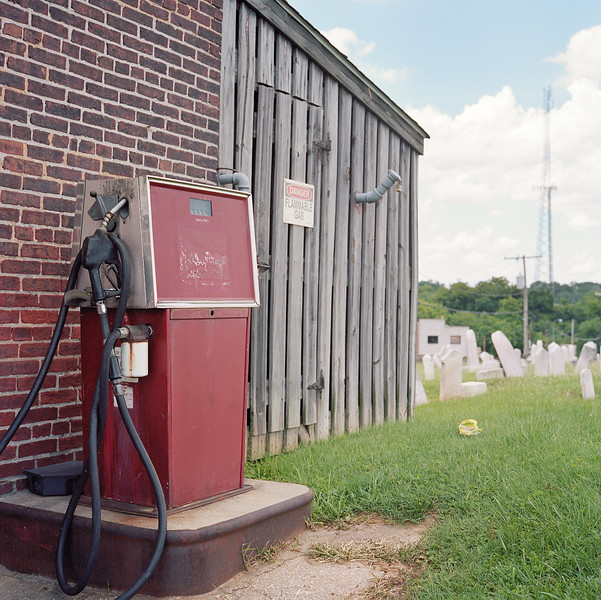 Old red gas pump, gravestones and radio tower in the Baltimore Cemetery