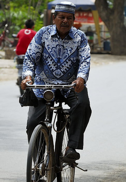 Resplendant in his fine Batik, a cyclist makes his way home from the market.