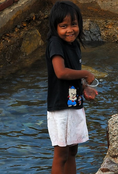 A young Acehnese girl tries her hand at fishing with a cup.