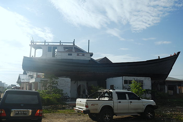 A fishing boat still sits on the roof of a house after being thrown about a kilometre inland by the tsunami.