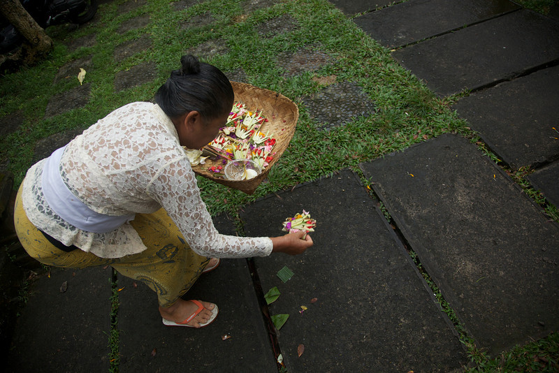 Laying small offering baskets called 'canang sari ' that Balinese offer to their Gods three times a day