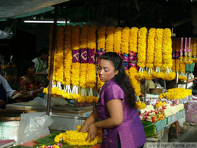 A woman prepares garlands for sale