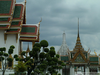 Three different types of temple and finely sculpted trees at the Grand Palace