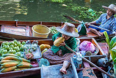 Inspecting her produce at the Damnoen Saduak floating market