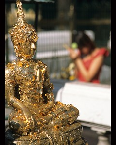 Golden Flake Buddha and women praying Grand Palace Bangkok, Thailand