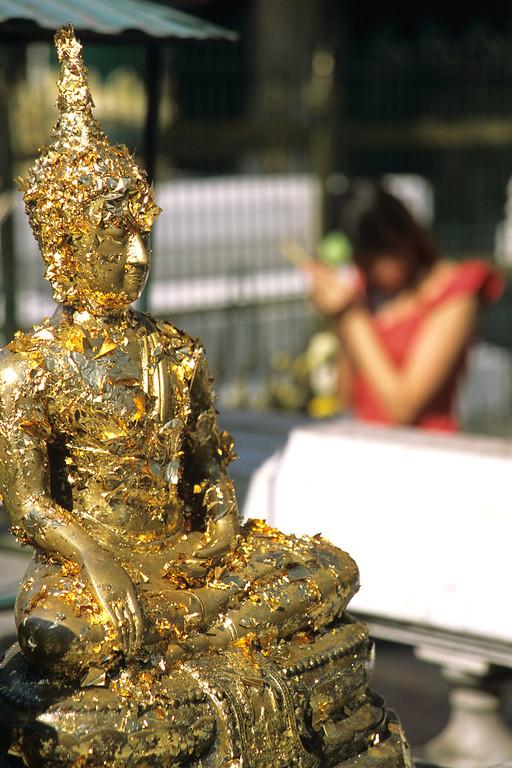 Golden flake buddha with praying Thai women, Bangkok Thailand
