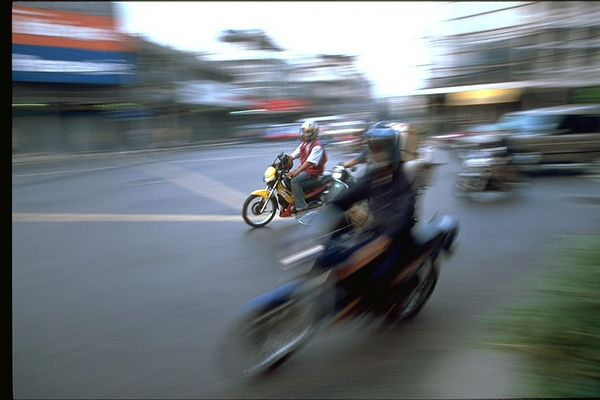 Moto scooters zooming Bangkok, Thailand