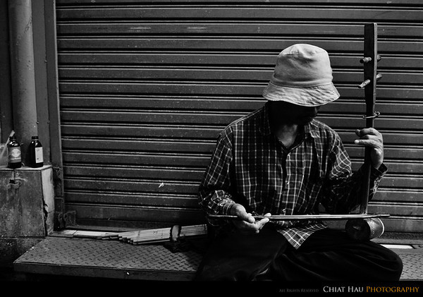 A lonely musician playing to earn a living