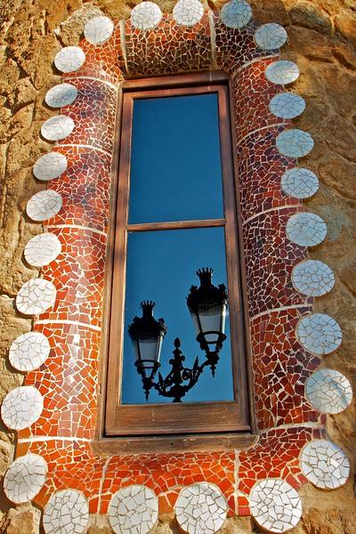 The crown at the top of the reflected street lights are the symbol of Barcelona.  The window is in the guardhouse at the entrance of Parc Guell