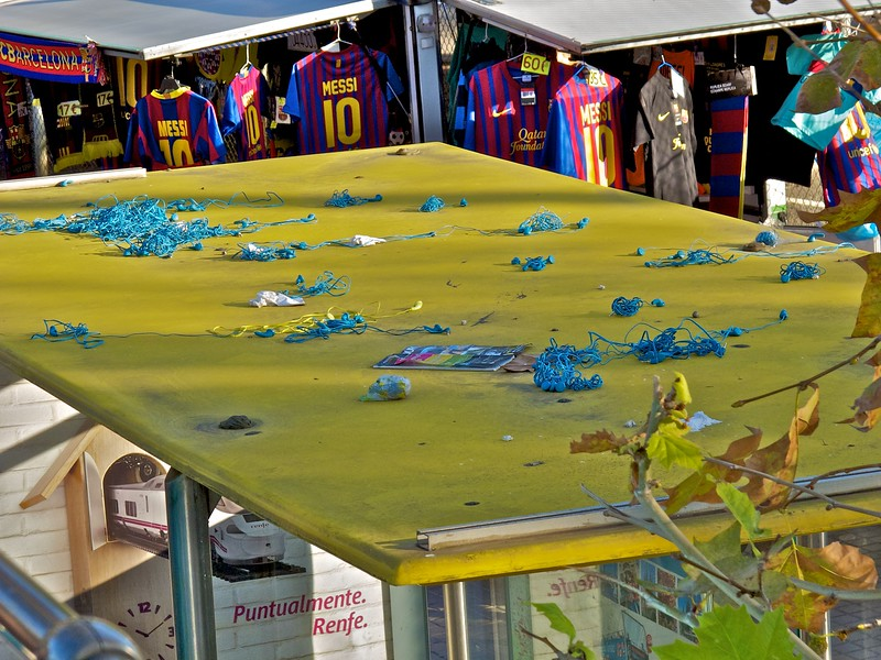 A Bus Turistic bus shelter with blue earbuds covering the roof.... a common way to dispose of the complimentary earbuds...  This is at the Barcelona football (soccer) stadium with booths in the background selling Barcelona FC (Barca) gear.