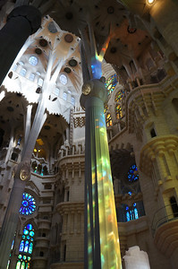 The sanctuary of La Sagrada Família with the light through the stained glass windows 'painting' the room in brilliant colors.