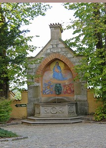 Madonna with baby Christ fountain containing both the coat of arms of Bavaria and Prussia.