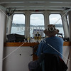 Boat captain steers toward the Russell Island in Bay of Islands, New Zealand.