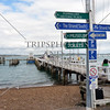 Directional signs along the wharf of Russell island in Bay of Islands, New Zealand.
