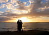 Young couple enjoying a picture perfect sunset at Sunset Cliffs, in San Diego, California.