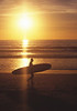 Surfer and sunset on the beach in San Diego.