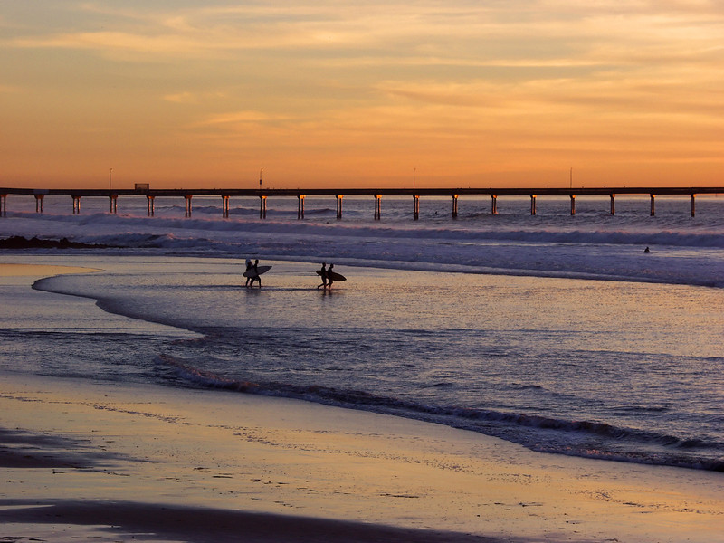 Surfers in Ocean Beach head out to the surf at sunset.