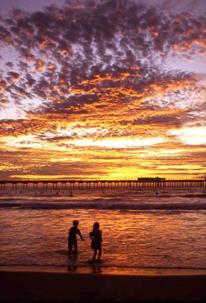 Children play in the surf as the sun goes down in Ocean Beach.
