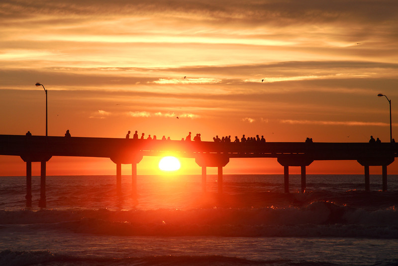 The Ocean Beach pier draws a crowd as the sun sets.