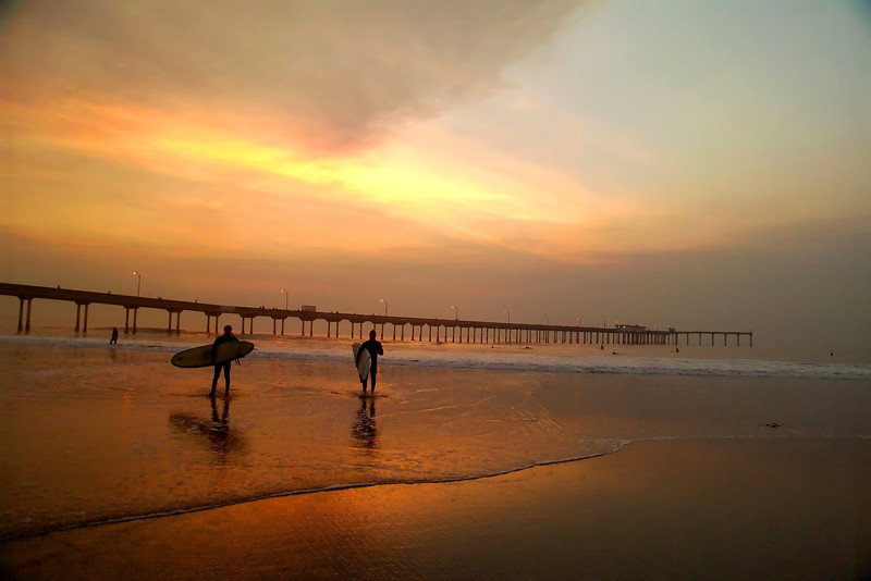 Surfers leaving the water at sunset after another great session at the Ocean Beach Pier, in San Diego, California.